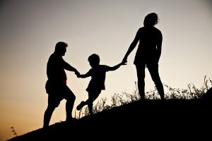 A silhouette of a child and the parents having fun.