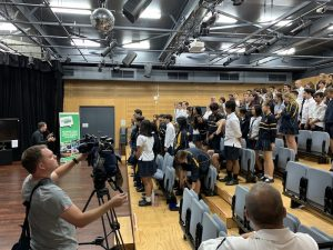 The presenter speaks to a class of Year 11 students, as a camera operator films.